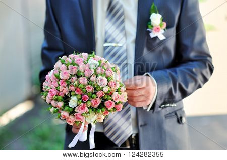 groom is holding a wedding bouquet in park