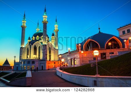 Inside Kazan Kremlin Russia. Aerial view of illuminated Qol Sharif Mosque and other historical buildings during at sunset .Colorful yellow and blue cloudy sky