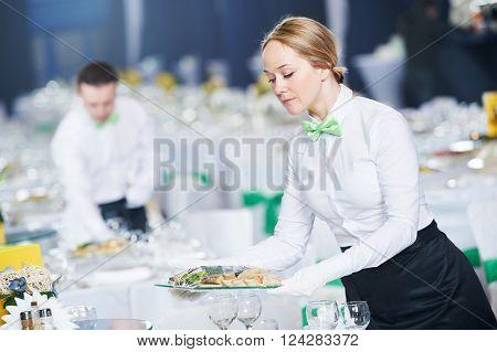 Restaurant services. Female waitress serving table