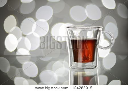 Espresso coffee in transparent mug on blurred lights background