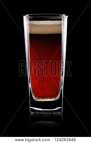 Carbonated brown cola beverage in glass on black background