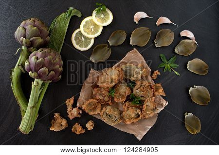 Top view of table with fried artichokes on kitchen paper, decorated with slices of lemon, mint leaves and garlic.