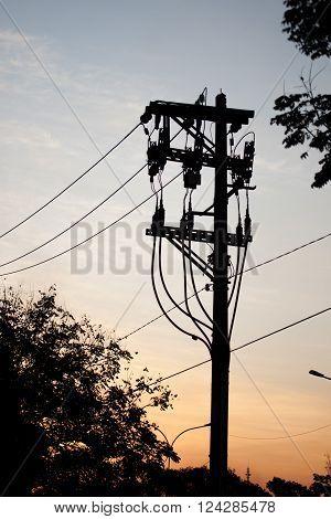 Electricity pole silhouette on sunset city scene