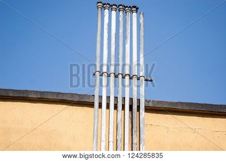Seven small chimneys pipe on yellow wall with blue sky