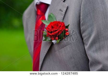Red Rose boutonniere on grey suit of groom in wedding day