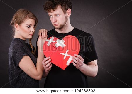 Sad Couple Holds Broken Heart.