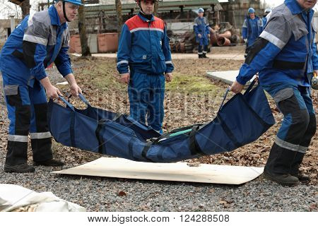 IVANGOROD, LENINGRAD OBLAST, RUSSIA - MARCH 29, 2016: Rescue team with dummy during the emergency training at Narvskaya Hydroelectric Power Plant. Built in 1956, it has nameplate capacity 125 MW