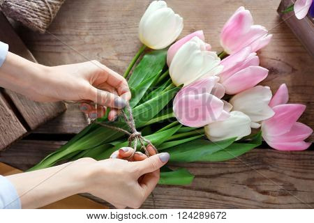 Female hands binding pink and white tulips with rope on wooden background