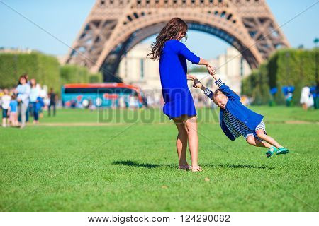 Happy mother and little adorable girl traveling in Paris near Eiffel Tower