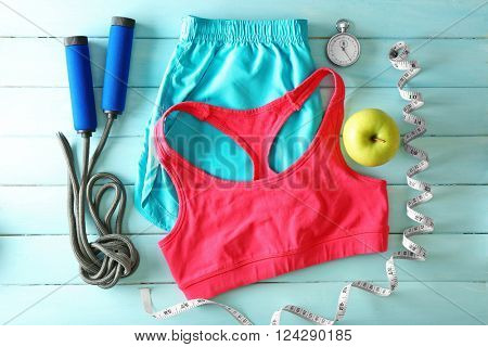Athlete's set with female clothing, equipment and apple on blue wooden background