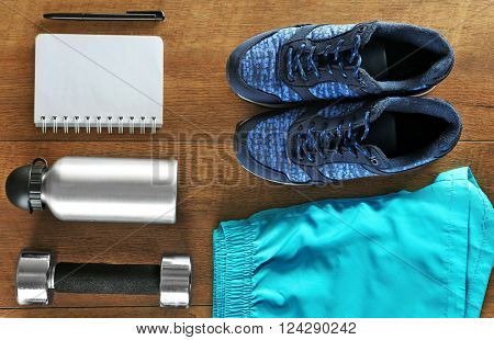Athlete's set with female clothing, dumbbells and notebook on wooden background