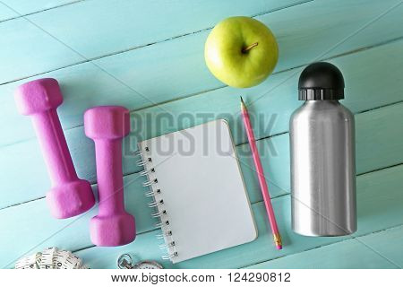 Athlete's set with dumbbells, apple, bottle of water and notebook on blue wooden background