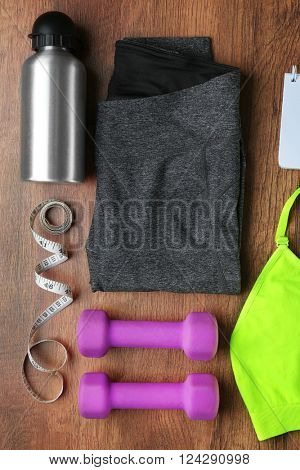 Athlete's set with female clothing, bottle of water, dumbbells and tape centimeter on wooden background