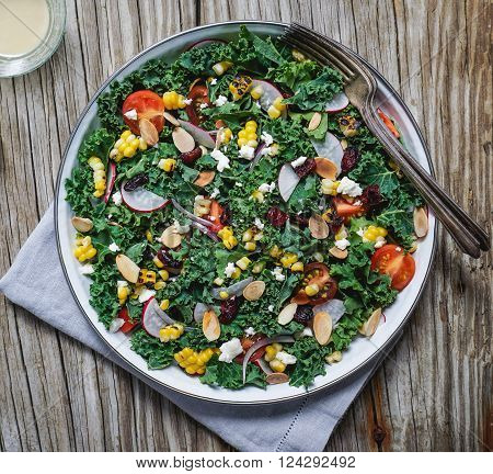 Chopped kale, grilled corn, tomatoes, dried cranberries and nuts salad on wood background/ Selective focus