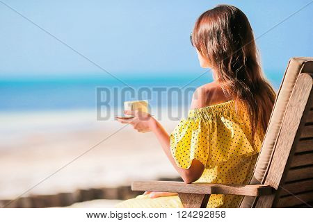 Young woman drinking coffee enjoying beach view