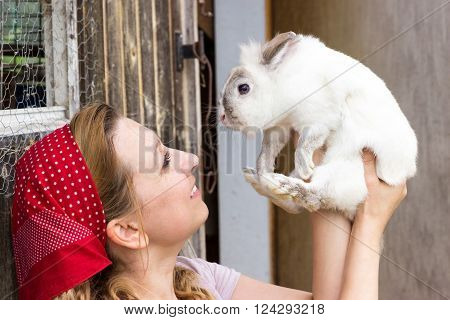 A peasant woman holding a white rabbit in the air