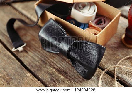 Black bow tie and full cardboard gift box of ties on wooden table, close up