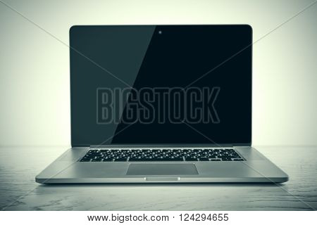 Laptop with black screen on white wooden table against white background
