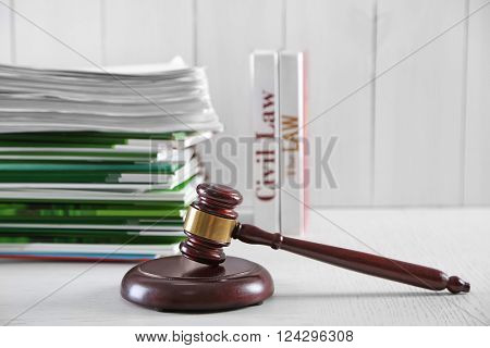 Gavel with stack of notebooks on wooden background