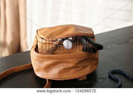 Backpack with makeup brushes and nail polish on wooden table indoors