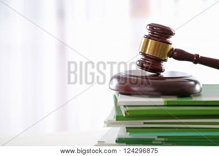 Gavel with stack of notebooks on light blurred background