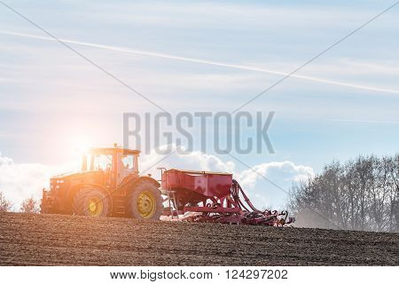 Beatiful sunset above the tractor harrowing the field in spring season