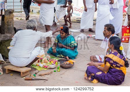 Trichy, India - October 15, 2013: Religious ritual to promote conceiving and pregnancy at Amma Mandapam. A flame has been lighted and family members watch. Here, the guru touches the head of the young woman with an orange, simplified image of a human.