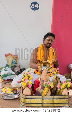 Trichy, India - October 15, 2013: Young Guru #34 sits in line and waits for clients at Amma Mandapam. A basket with offerings to be bought stands in front. He wears a white dhoti and an orange shawl.