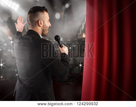 Man talking on microphone on theater stage