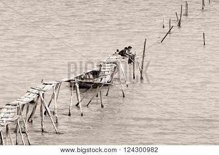ALAT, AZERBAIJAN - APRIL 14 2014  Boys fishing in Caspian Sea on broken pier. Alat lies south east of Baku, along Azerbaijan's coast, and fishing is a popular pastime