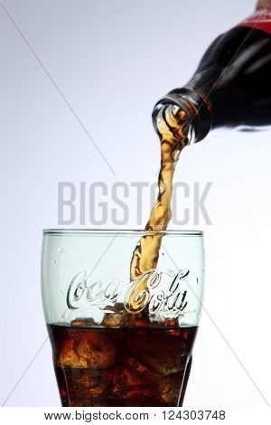 KUALA LUMPUR, MALAYSIA - Feb 17, 2016 pouring coca cola to a glass with ice cube