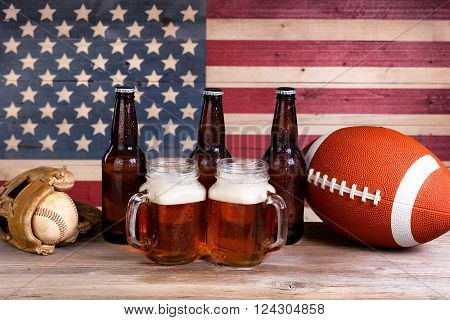 Two pint jars filled with beer full bottles football and baseball mitt with vintage wooden USA flag in background.