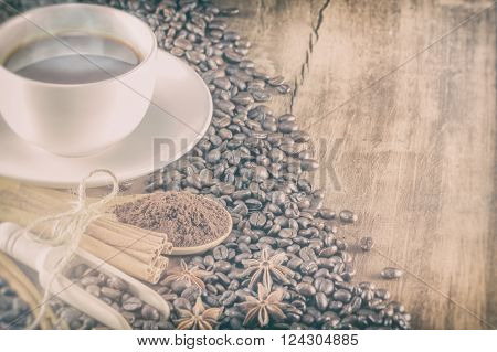 coffee on the cup with coffee beans and cinnamon sticks selective focus vintage toning