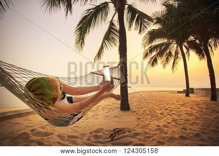 woman lying in beach cradle and taking a photograph by smart phone