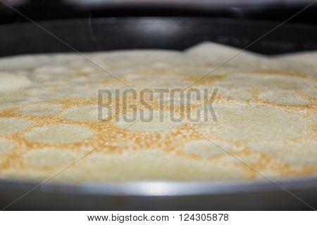 Frying pan with pancake baking on it