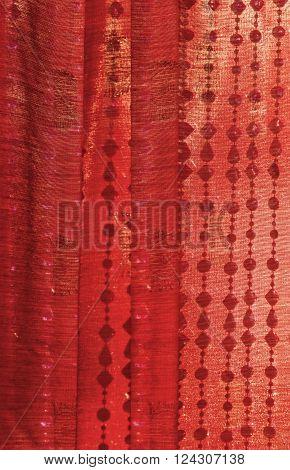 Closeup of red Indian Sari silk curtain with hanging beads/Background of Red Indian sari curtain with hanging beads