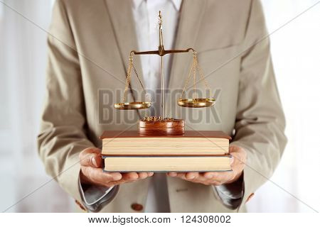 Man holding books with scales of justice indoors