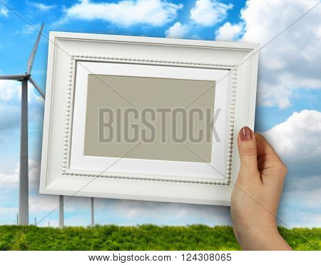 Wooden frame in beautiful woman hands. wind mill turbine in a farmland on the background