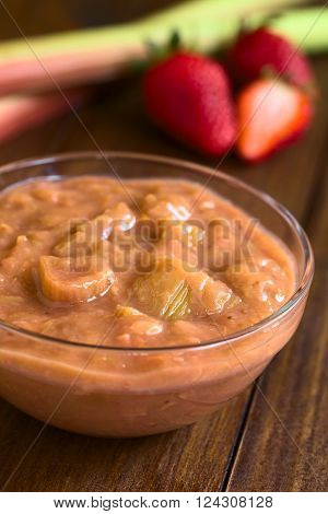 Homemade rhubarb and strawberry chutney in glass bowl, photographed on dark wood with natural light (Selective Focus, Focus one third into the chutney)
