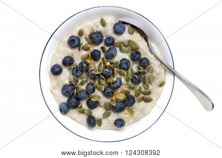Oatmeal or porridge with blueberries, pepitas and honey.  Overhead view with spoon, isolated on white.