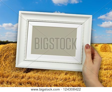Wooden frame in beautiful woman hands on the background of Hay bales sitting in a field