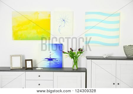 Modern living room interior with white lockers and canvases on the white wall