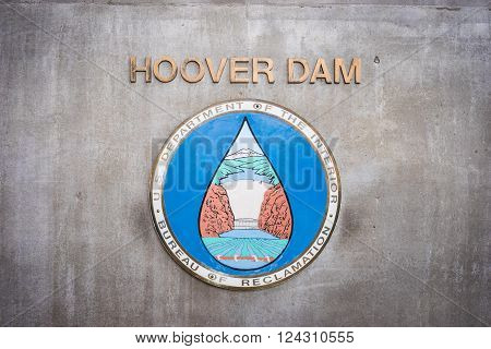 Logo and insignia hanging from the side of a Hoover Dam building.