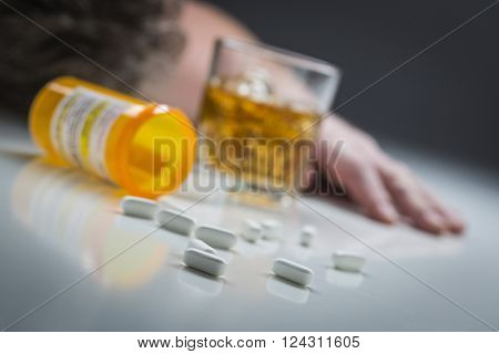 Unconscious Man Face Down Behind Scattered Prescription Drugs and Glass of Alcohol.