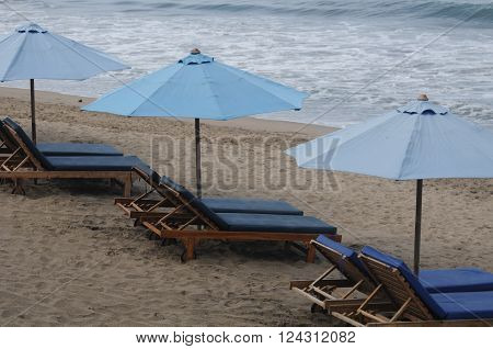 Three umbrellas lined place to relax on the beach with a lay underneath
