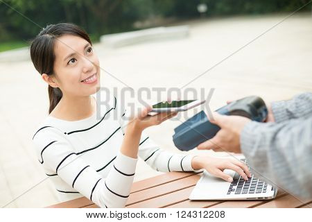 Woman paying by mobile phone with NFC technology