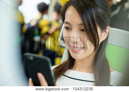 Woman using smartphone inside train compartment