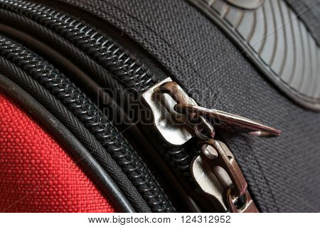 two zipper on red and black luggage back