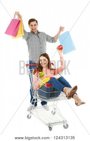 Man carrying woman in metal trolley with products and colorful shopping bags isolated on white