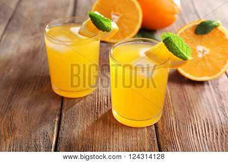 Two orange juices with ice and orange on wooden table background